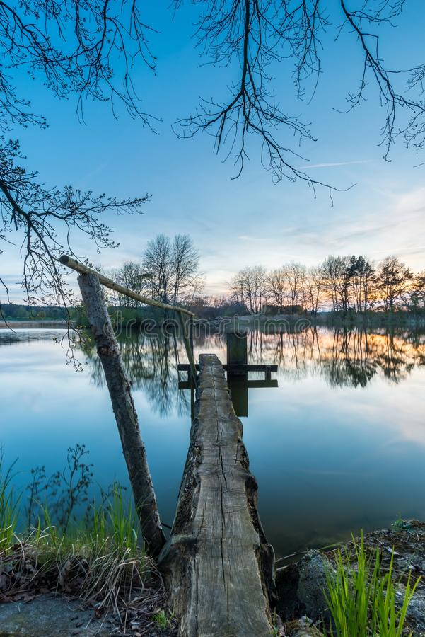 Old wooden floodgate with wooden bridge over the pond royalty free stock images