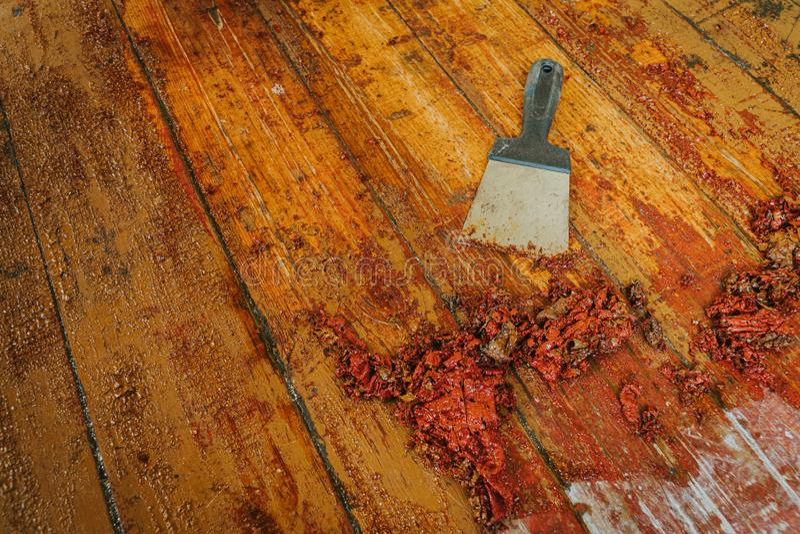 Old wooden floor and scraper tool with paint scraped - wooden floor renovation.  stock image