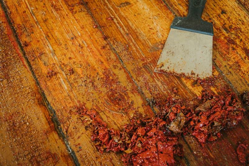Old wooden floor and scraper tool with paint scraped - wooden floor renovation.  stock photography