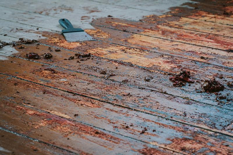 Old wooden floor and scraper tool with paint scraped. Wooden floor renovation royalty free stock images