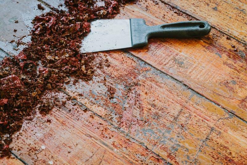 Old wooden floor and scraper tool with paint scraped. Floor renovation stock photos