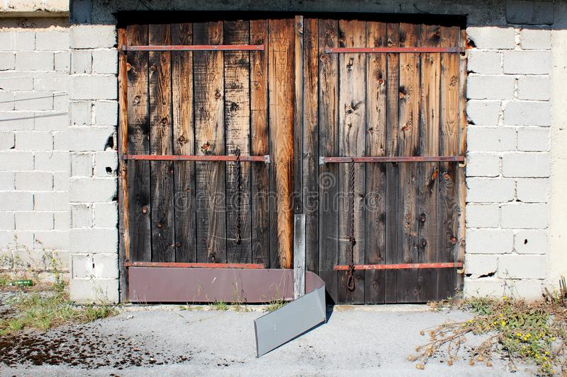 Old wooden garage doors with faded wooden boards and broken metal protection mounted on abandoned outdoor storage building stock photo