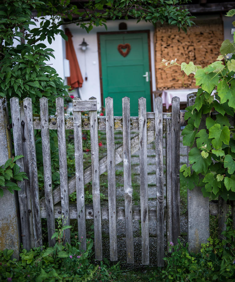 Old wooden garden gate. On the background a door with a hart royalty free stock photography