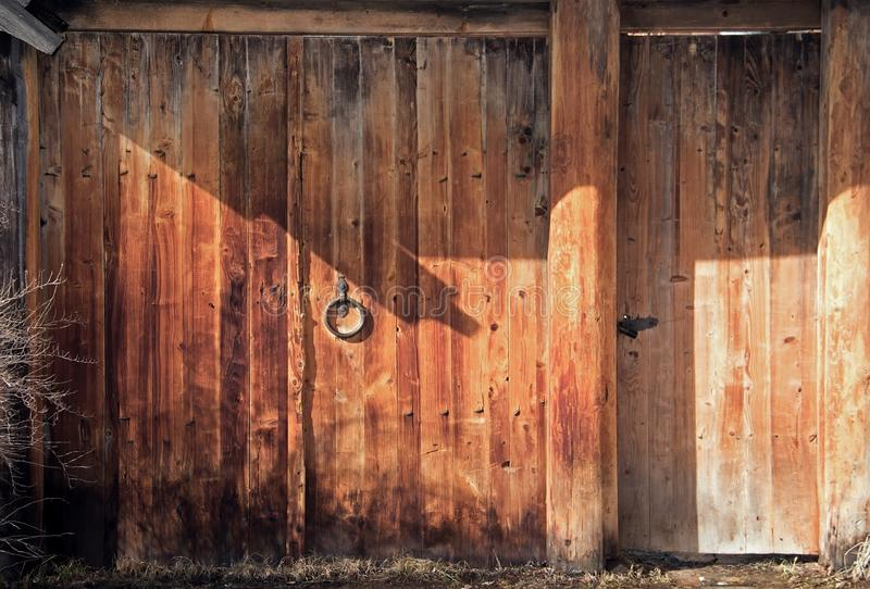 Old wooden gate with a metal handle. Dark orange wood background royalty free stock photography
