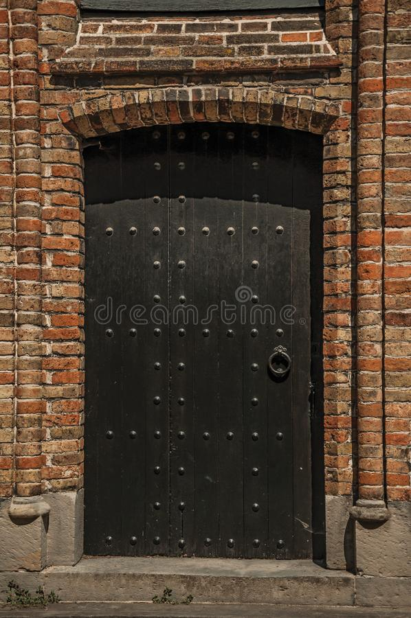 Old wooden gateway on gothic church in alley of Bruges stock photo