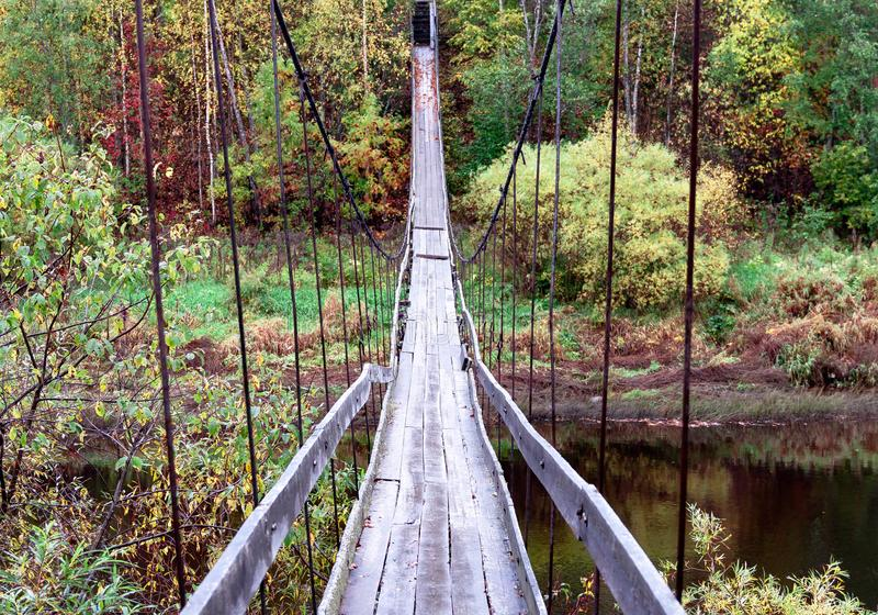 Old wooden handmade suspension hanging bridge over the river on a natural autumn background stock photography
