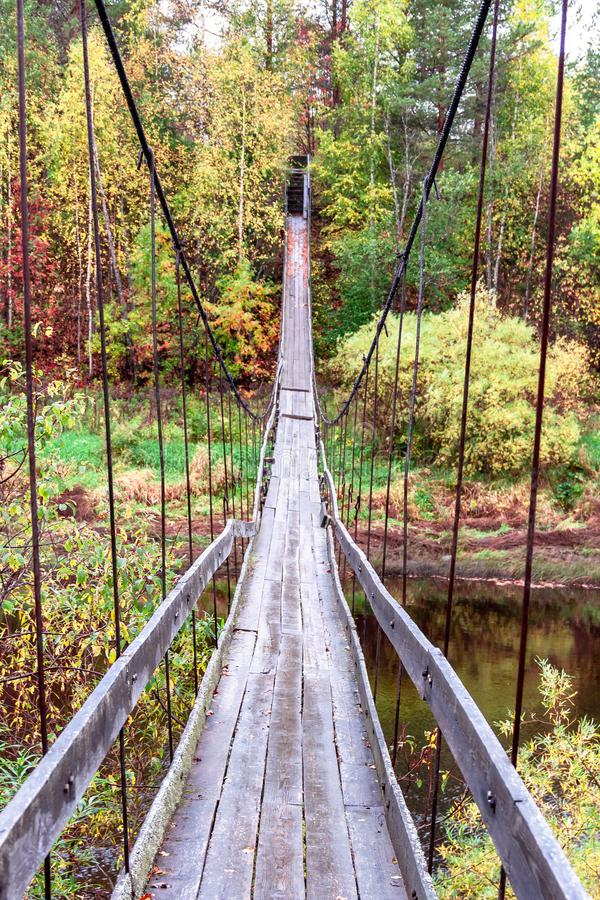 Old wooden handmade suspension hanging bridge over the river on a natural autumn background stock images