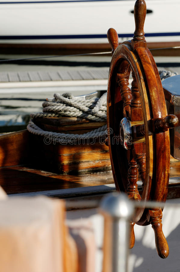 Old wooden helm. An old weathered wooden helm on a boat royalty free stock photos