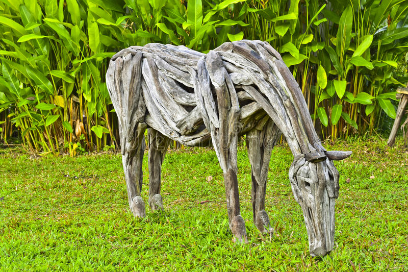 Old wooden horse in lush tropical garden, Horse made of scrap wood royalty free stock photo