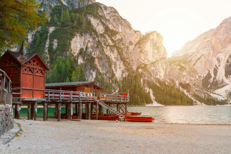 Old wooden house on the Braies lake in the background of Seekofel mountain. In Dolomites,Italy Pragser Wildsee stock photo