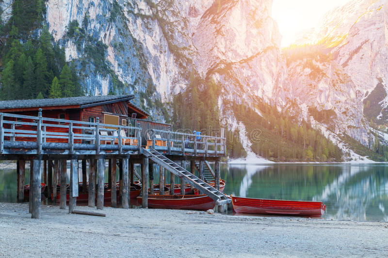 Old wooden house on the Braies lake in the background of Seekofel mountain. In Dolomites,Italy Pragser Wildsee stock image