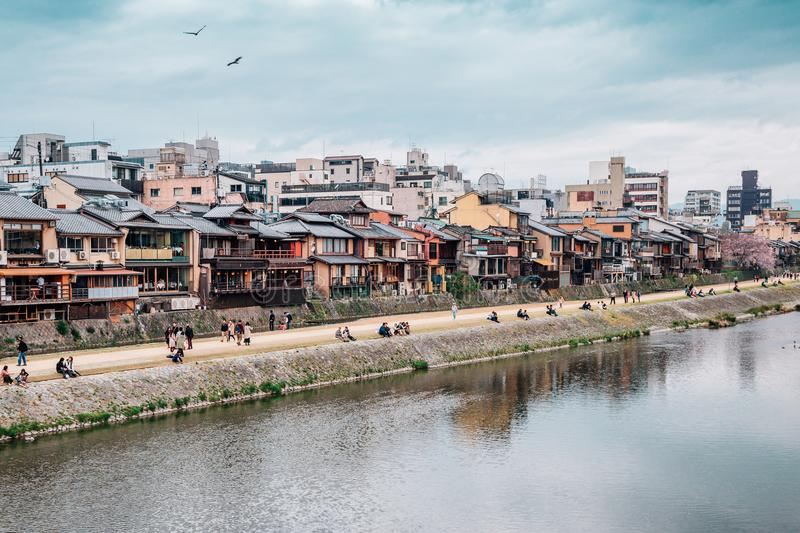 Old wooden house with cherry blossom and Kamo river at Gion street in Kyoto, Japan royalty free stock photo