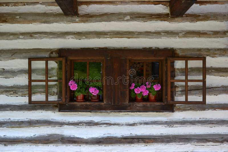 Old wooden house with flowers in the window royalty free stock photo