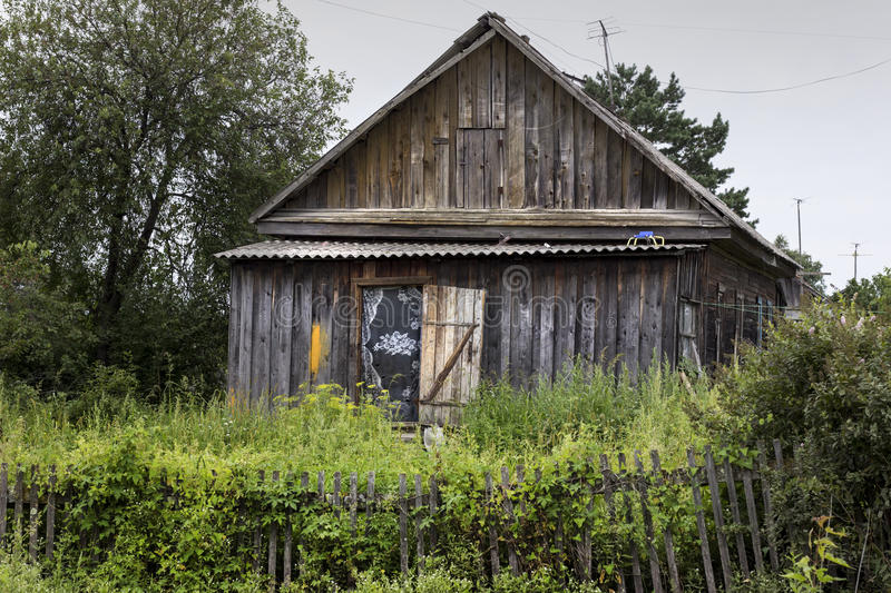 Old wooden house with grassy fence. Poor village mansion with op stock images