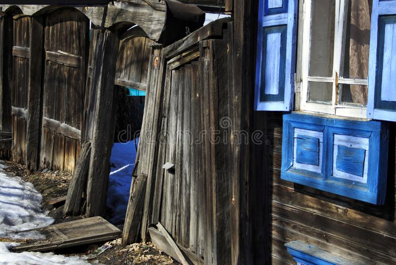 Old wooden house with open shutters painted blue with a rickety gate and gate stock images