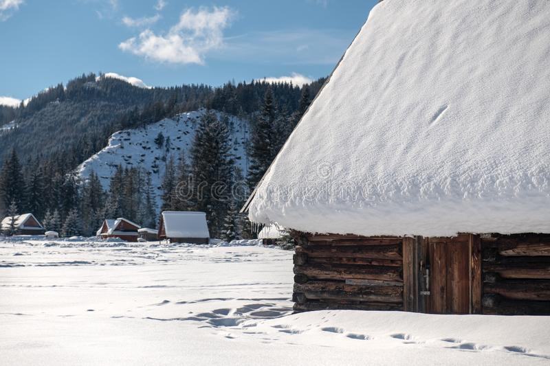 Old wooden house by the road in a beautiful winter scenery. Huge icicles hang from the roof. stock images