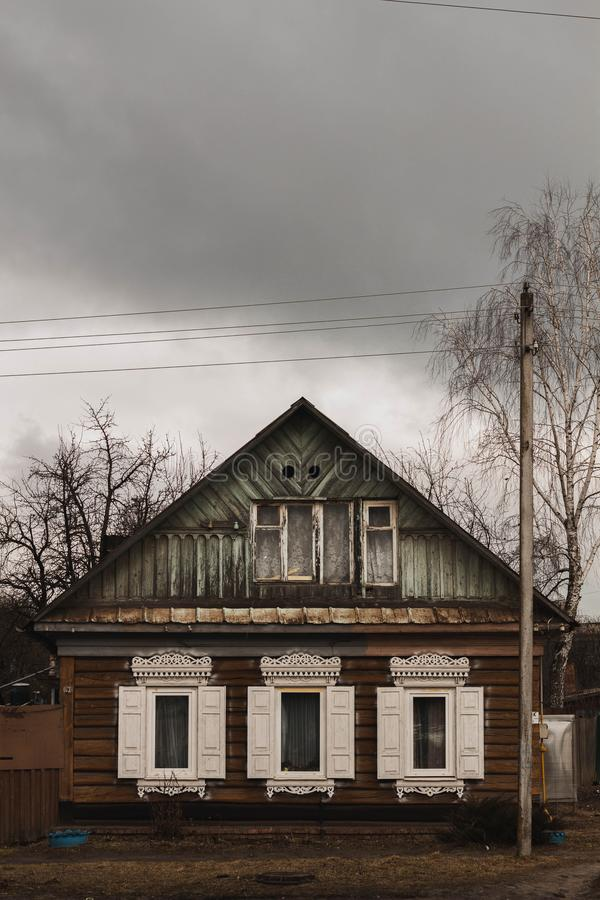 Old wooden house with white shutters in cloudy weather stock photos