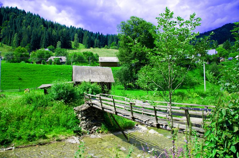 Old wooden houses on a background of mountains and forest. A wooden bridge royalty free stock image