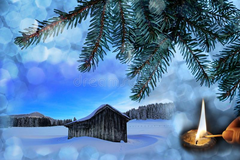 An old wooden hut in the snow with Christmas snowflakes, fir branches and a burning candle. Christmas background stock photos