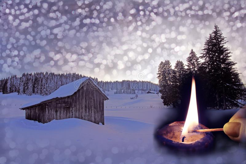 An old wooden hut in the snow with Christmas snowflakes, fir branches and a burning candle. Christmas background royalty free stock photography