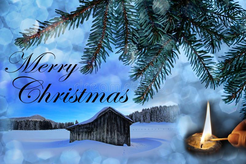 An old wooden hut in the snow with Christmas snowflakes, fir branches and a burning candle. Christmas background royalty free stock images