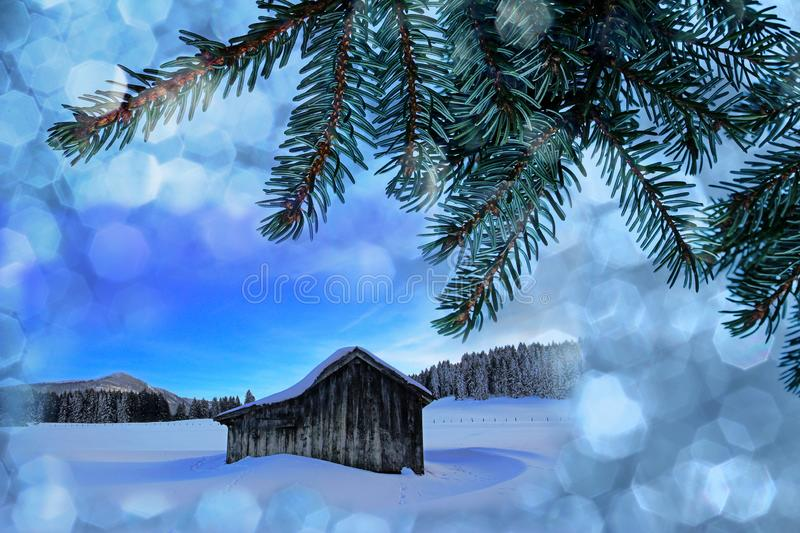 An old wooden hut in the snow with Christmas snowflakes and fir branches stock photography