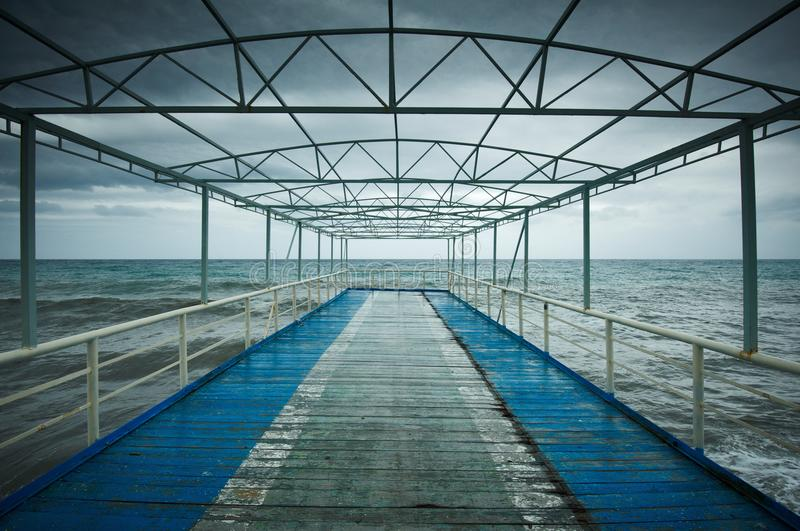 Old wooden jetty, pier, during storm on the sea. Dramatic sky with dark, heavy clouds. Vintage stock photos