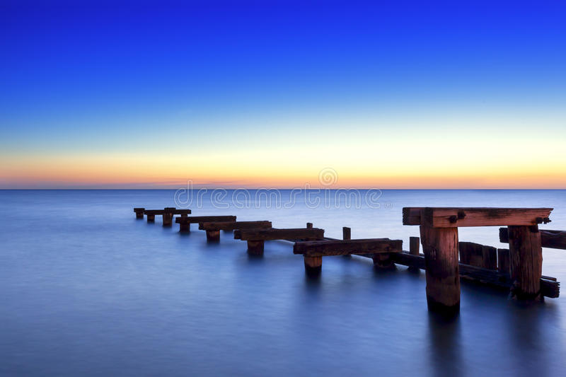 Old Wooden Jetty at Sunset. Over peaceful bay stock photos