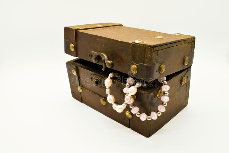 Old wooden jewelry chest with pearl bracelet isolated on white background. Treasure gold closeup box accessory coin furniture antique decorative design brown royalty free stock images