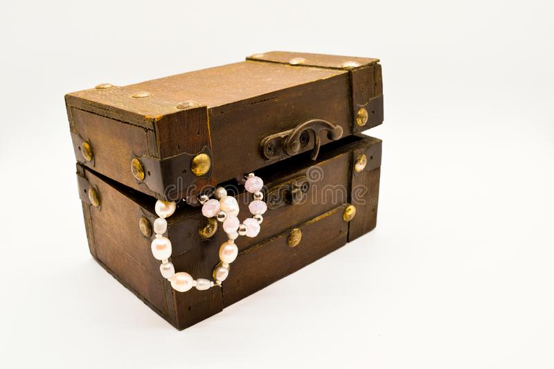 Old wooden jewelry chest with pearl bracelet isolated on white background. Treasure gold closeup box accessory coin furniture antique decorative design brown stock images