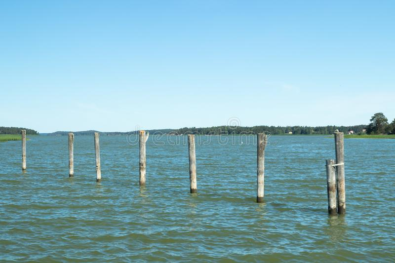 Old wooden logs in the sea in harbor of Naantali, Finland.  royalty free stock photos