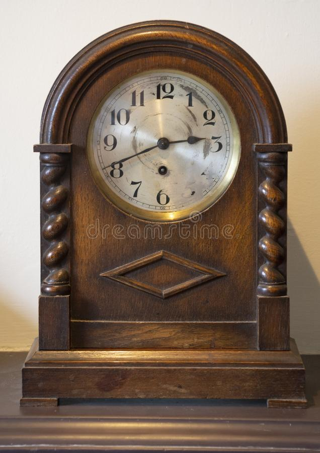 Old Wooden Mantel Clock. With carved wood relief on wooden mantel showing 20 to 3 with worn and marked clock face stock photography
