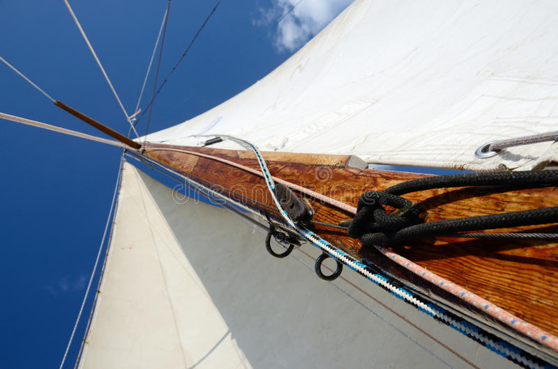 Old wooden mast with crosspieces, backstays,mainsail ,staysail stock photo