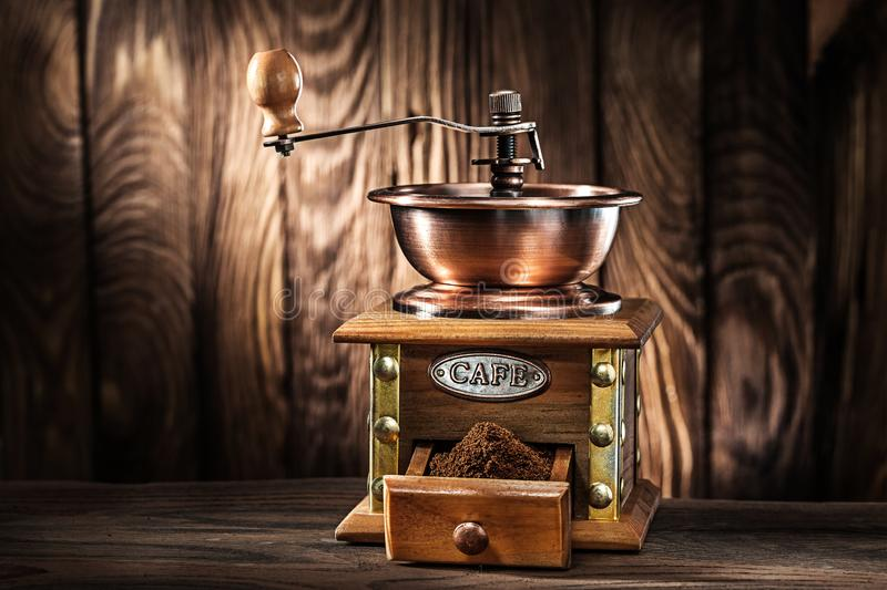 Old wooden mill with coffee sand on vintage wooden background stock photos