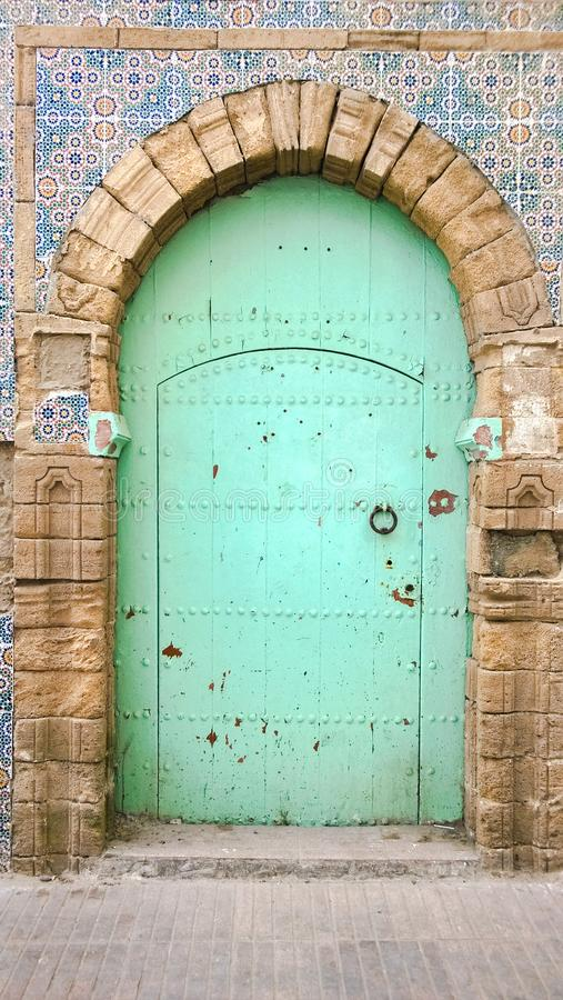 Old wooden Moroccan door with a faded blue green color, Essaouira, Morocco royalty free stock image