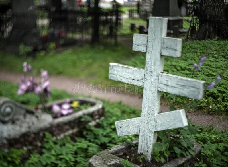 Old wooden orthodox grave cross in a cemetery with a blurry background with flowers and grave fences royalty free stock photography