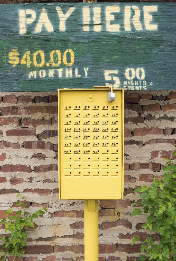 Pay Here. Old wooden painted sign with words PAY HERE, $40.00 monthly, $5.00 nights, evenings with vintage yellow fee box with coin slots stock photos