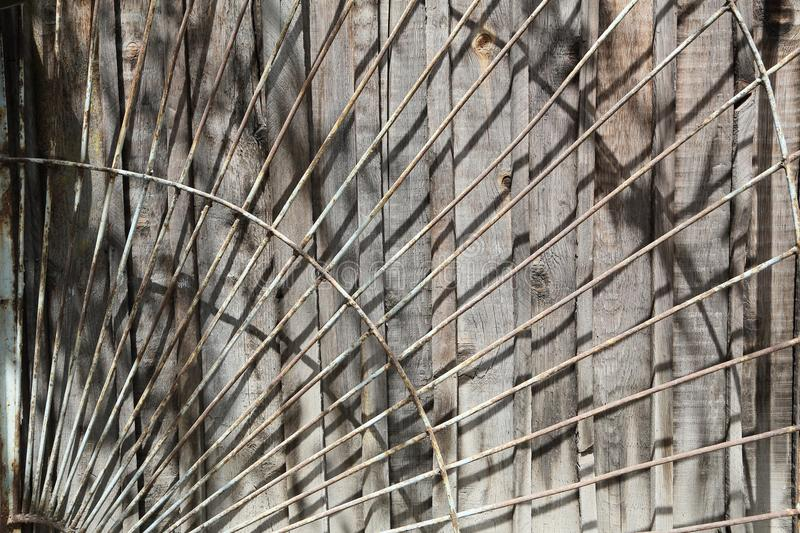 The rough Board behind bars. Old wooden panel under the rusty iron bars royalty free stock photo