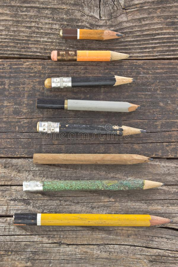 Old wooden pencils on wooden background stock photography