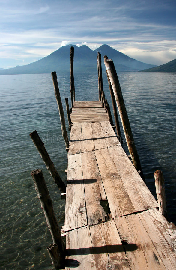 Old wooden pier. Jutts out into Lake Atitlan, volcanoes in background. Atitlan. Guatemala stock photo