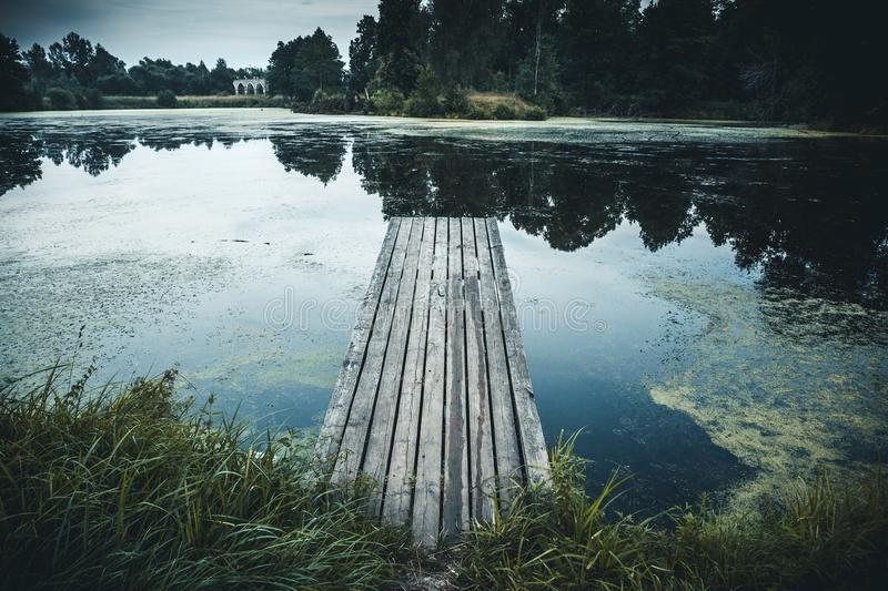 Old wooden pier in lake, Idyllic tranquil view nature background with reflection in water royalty free stock photography
