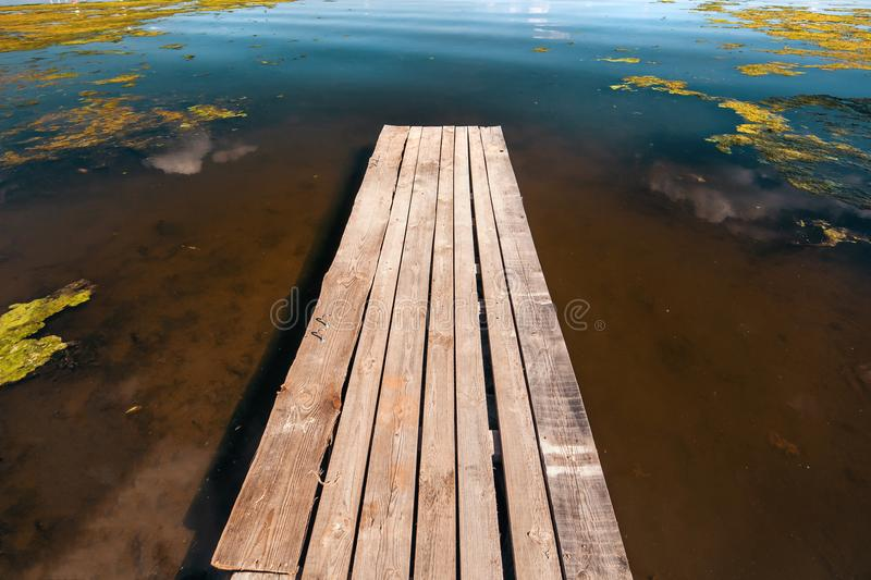 Old wooden pier on shore of lake or river with mud stock photo