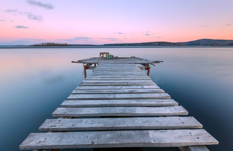 Old wooden pierat sunset. Old wooden pier at sunset, long exposuren royalty free stock images
