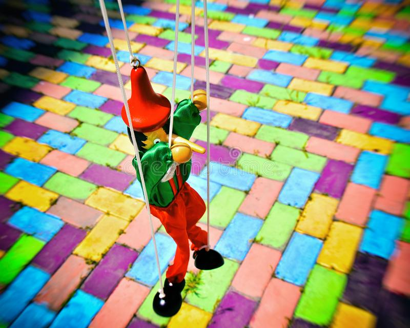 Old wooden pinocchio puppet. On a colorful tiles. Marionette retro toy royalty free stock photos