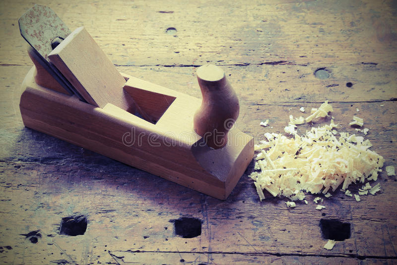 OLD wooden PLANE on the table. Of the workshop of carpenter with some shavings royalty free stock photography