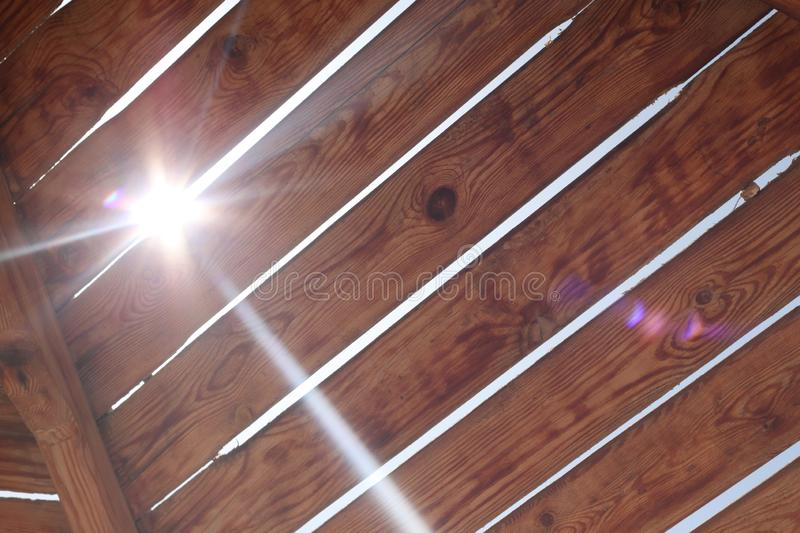 Old wooden boards through which the sun`s rays make their way royalty free stock image