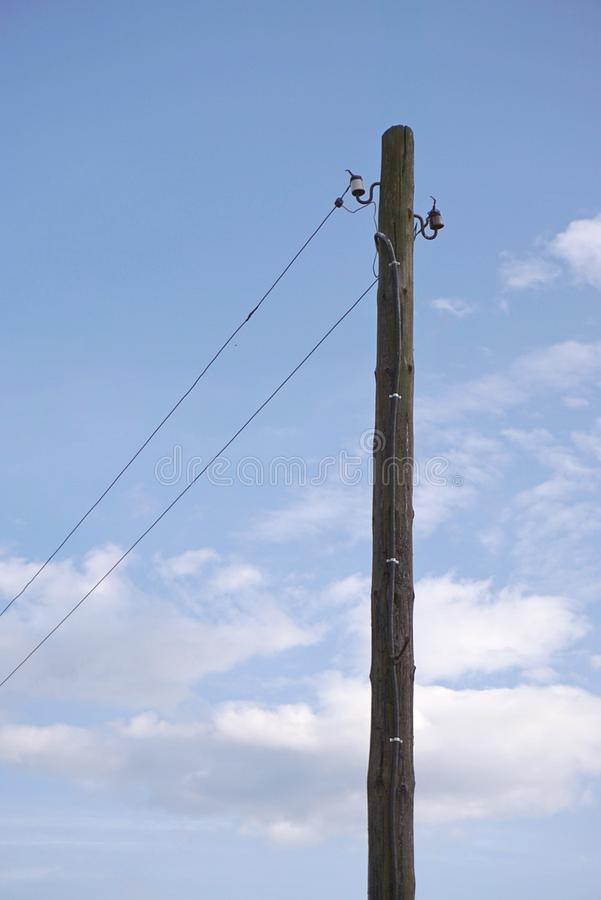 Old wooden power-transmission pole. Electric power line with dangling wires. Electric power line with dangling wires stock image