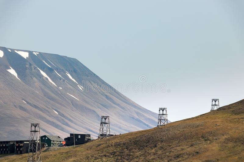 Old wooden pylons for coal-transport carts cables at the edge at Longyearbyen, Svalbard. Old wooden towers for cable-cart coal transport at summer in stock images