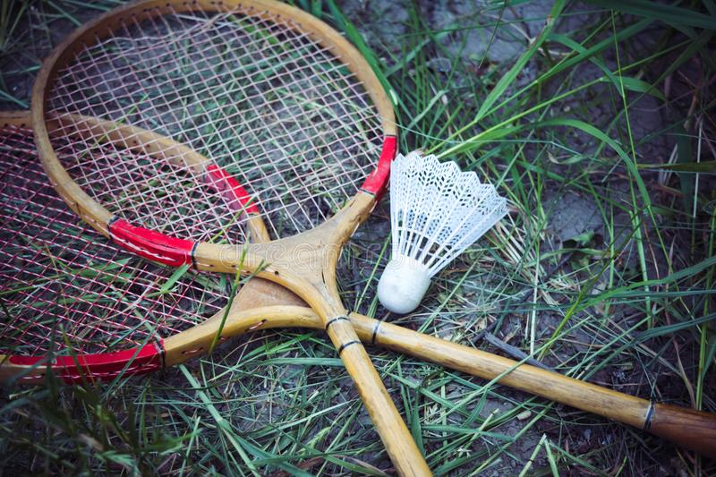 Old wooden rackets and shuttlecock lying on the grass. Sports games on picnic. royalty free stock photo