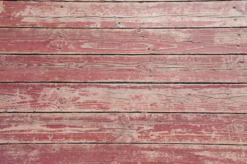Old wooden red floor texture closeup. Horizontal strips with peeling paint and nails. Outdoors royalty free stock photos
